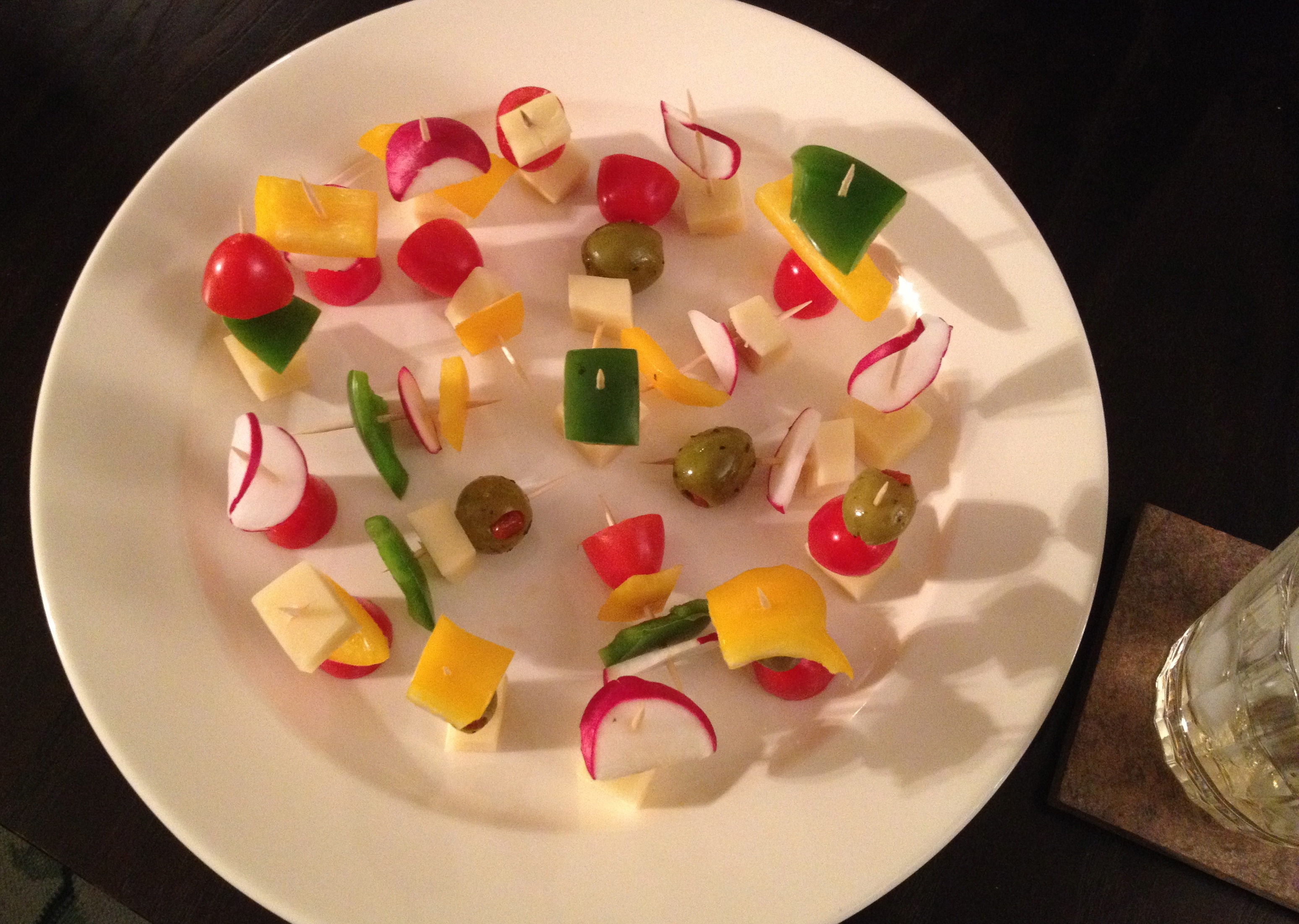 Small bites made up of gouda cheese cubes with radishes, green pepper, olives,  yellow pepper and cherry tomatoes on toothpicks
