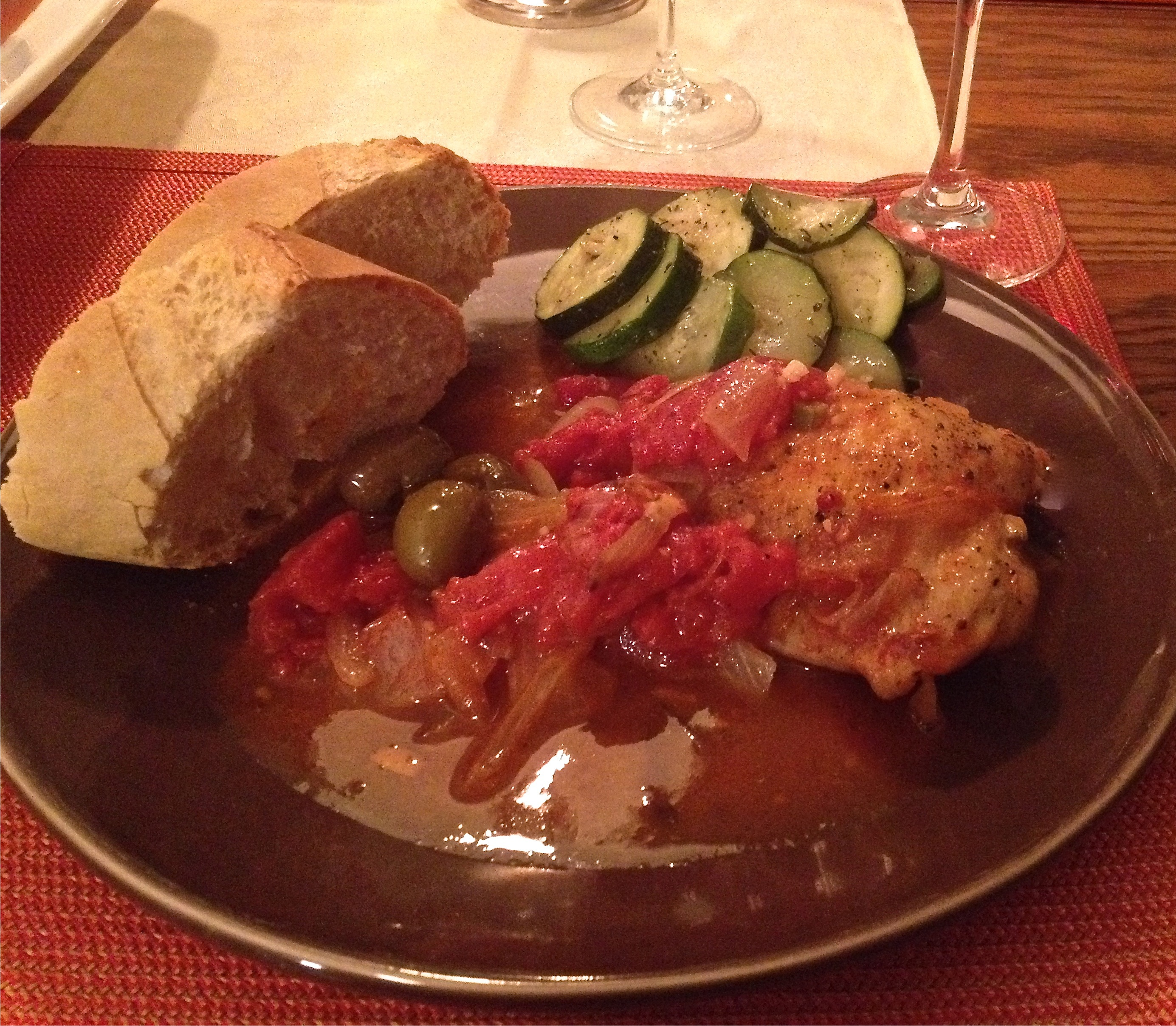 Braised chicken legs with tomatoes, onions, garlic, and olives on slices of a French baguette and roasted zucchini on a brown pottery plate.