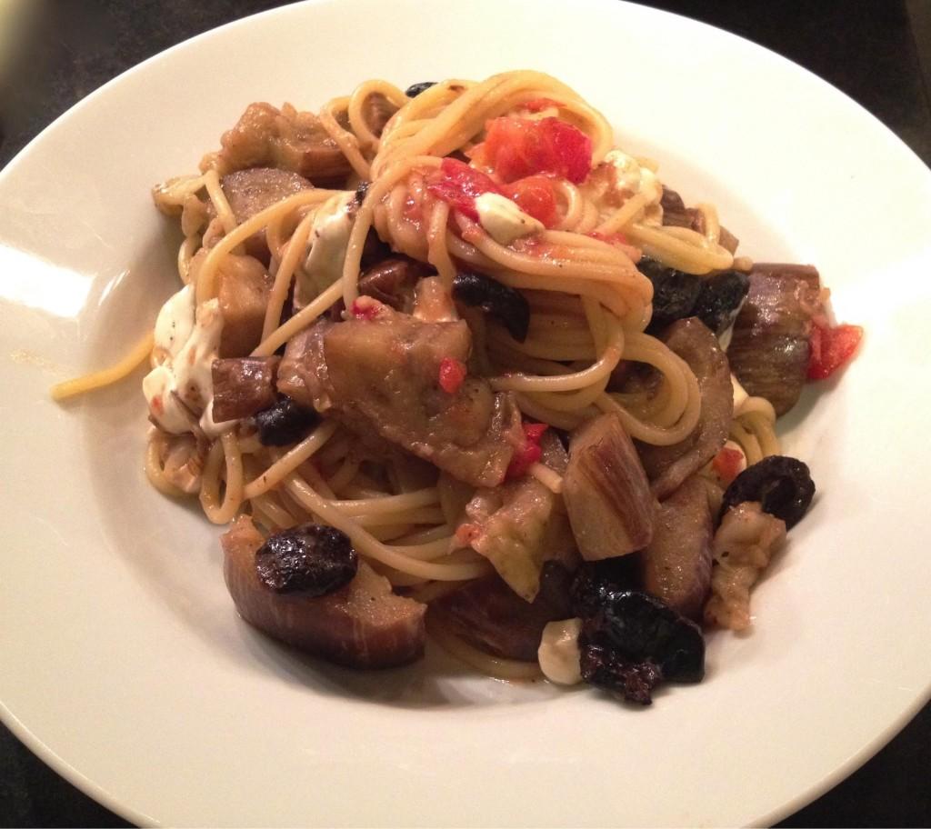 Eggplant mozzarella and oil cured black olive spaghetti finished in a bowl.