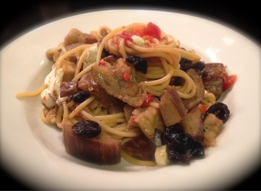 Eggplant mozzarella and oil-cured black olive spaghetti in a white bowl with blurred edges.