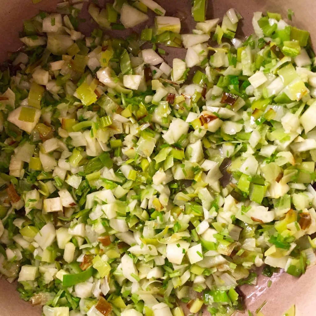 Browning leeks in a Le Creuset pot.