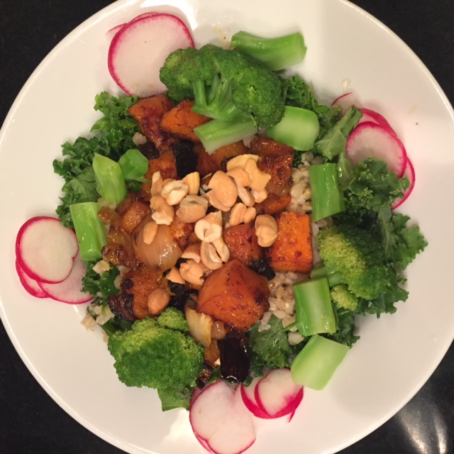Kale and farro salad with spicy butternut squash, broccoli, radishes and cashews in one white bowl.