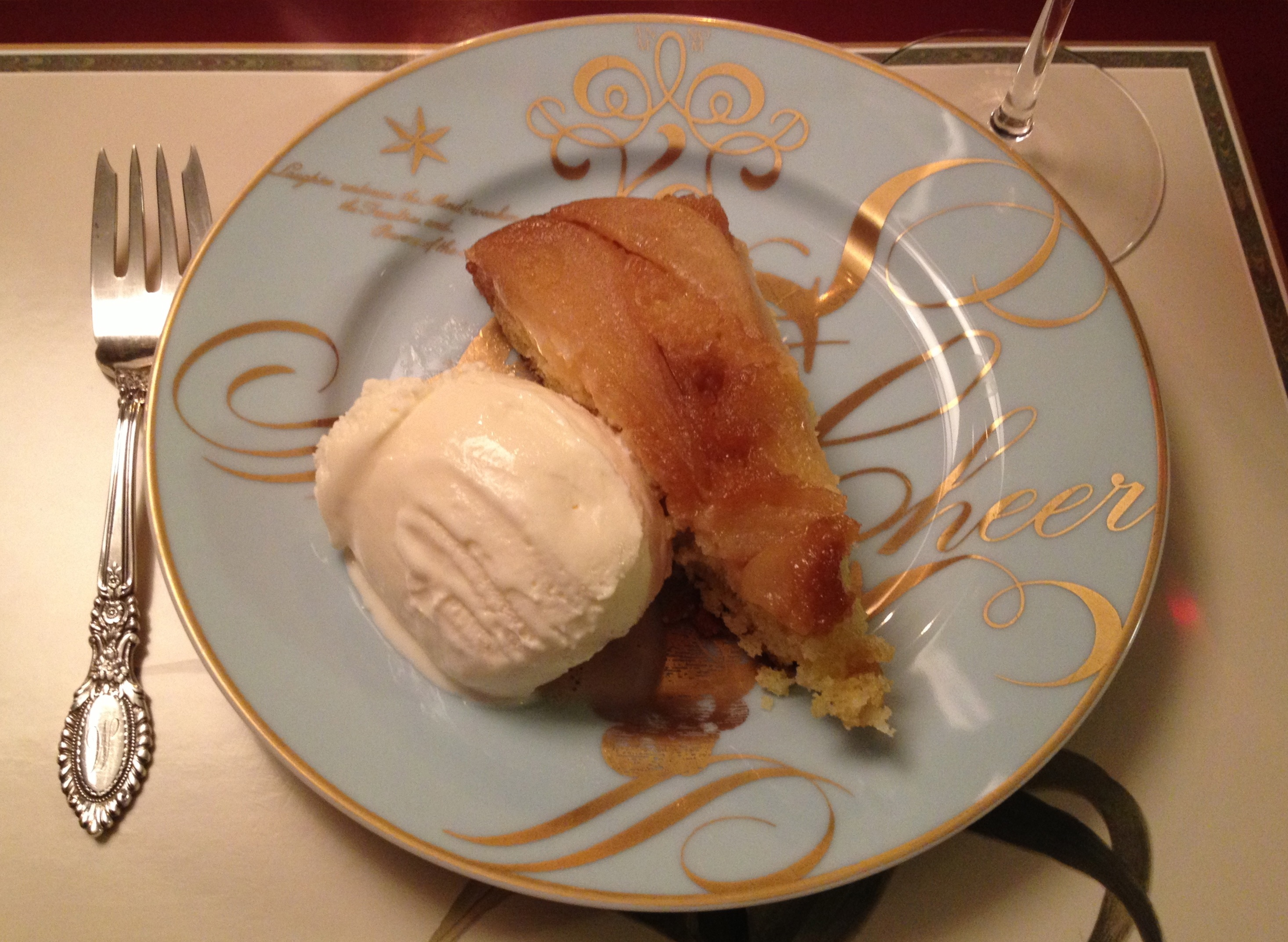 Slice of pear upside down cake with a small scoop of ice cream on a light blue plate from Williams Sonoma.